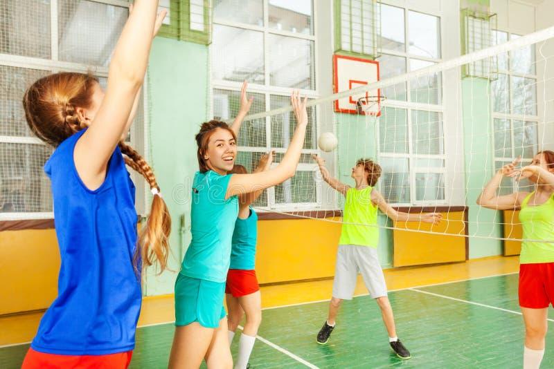 Έφηβη που πιάνει τη σφαίρα κατά τη διάρκεια της αντιστοιχίας πετοσφαίρισης στοκ φωτογραφία
