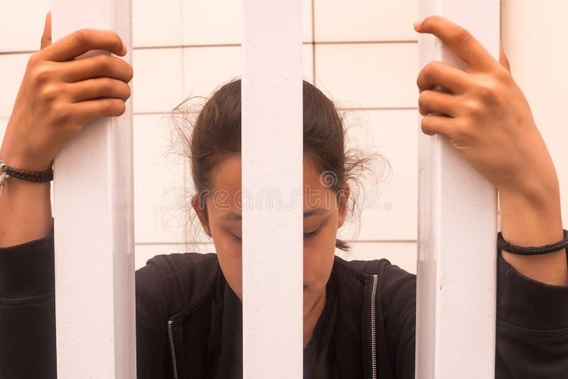 Έφηβη που φαίνεται ανησυχημένο δεδομένου ότι πιάνει τους φραγμούς στοκ εικόνες