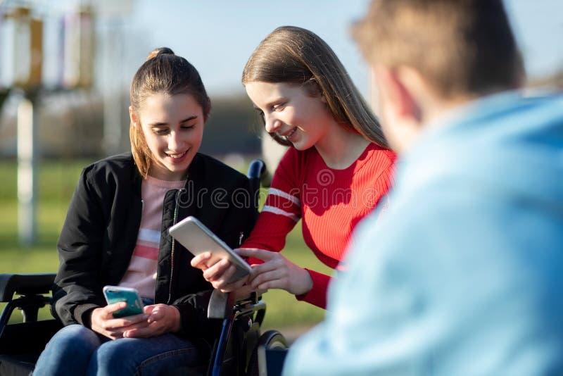 """Έφηβη στην αναπηρική καρέκλα με Ï""""Î¿Ï…Ï' φίλους που εξετάζουν τα κοινωνικΠστοκ εικόνες"""