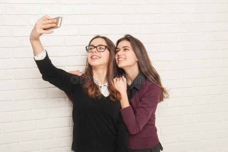 Έφηβοι κοριτσιών ενάντια σε έναν άσπρο τουβλότοιχο στοκ εικόνες