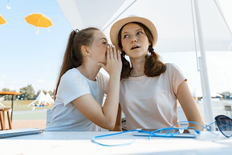 Έφηβοι κοριτσιών που έχουν τη διασκέδαση, συζήτηση, μυστικό, γέλιο Καθίστε σε έναν καφέ οδών, ηλιόλουστη θερινή ημέρα στην περιοχ στοκ φωτογραφία με δικαίωμα ελεύθερης χρήσης