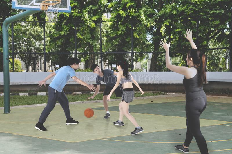 Έφηβοι που παίζουν την καλαθοσφαίριση μαζί υπαίθρια στοκ φωτογραφία