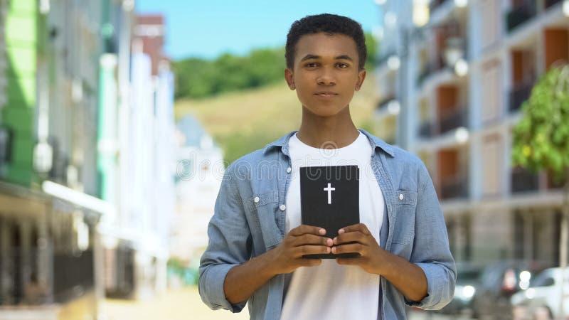 Έφηβος άντρας χριστιανός κρατά ιερή βίβλο κοντά στην καρδιά, την πίστη και τις πεποιθήσεις, τη θρησκεία στοκ εικόνα