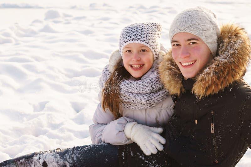 Έφηβος αδελφός και αδελφή διασκεδάζουν χιόνι το χειμώνα στοκ φωτογραφίες