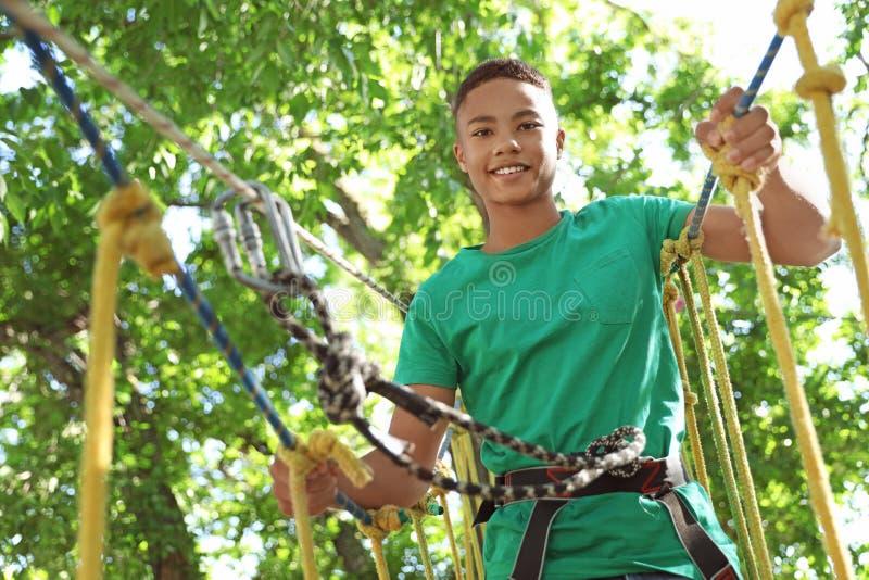 Έφηβος αφροαμερικάνων που αναρριχείται στο πάρκο περιπέτειας Καλοκαιρινό εκπαιδευτικό κάμπινγκ στοκ φωτογραφίες με δικαίωμα ελεύθερης χρήσης