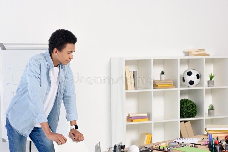 έφηβος αφροαμερικάνων που κλίνει στην καρέκλα και που εξετάζει τον πίνακα με τον τεχνικό εξοπλισμό στοκ φωτογραφίες με δικαίωμα ελεύθερης χρήσης