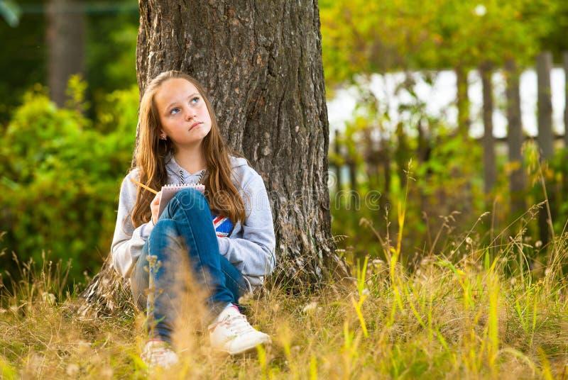 Έφηβος-κορίτσι που γράφει σε ένα σημειωματάριο στοκ εικόνα με δικαίωμα ελεύθερης χρήσης