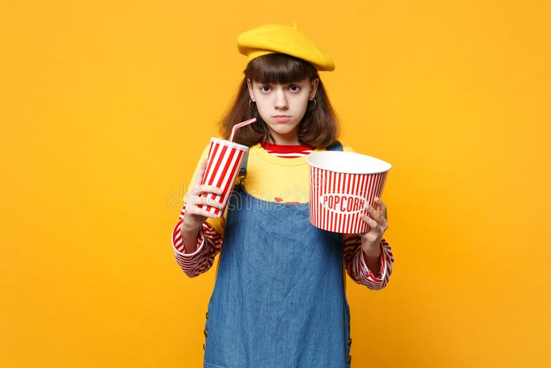 Έφηβος κοριτσιών γαλλικό beret, το πλαστικό φλυτζάνι εκμετάλλευσης τζιν sundress της κόλας ή τον κάδο σόδας popcorn που απομονώνε στοκ φωτογραφίες