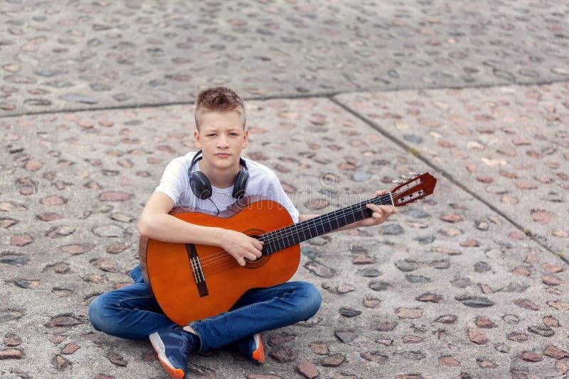 Έφηβος με την ακουστική κιθάρα και ακουστικά που κάθονται στο πάρκο στοκ εικόνες