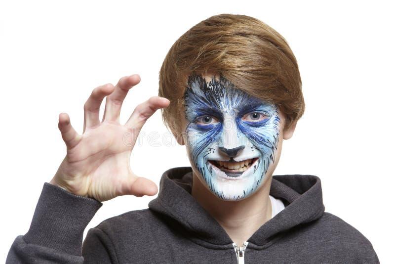Έφηβος με το λύκο ζωγραφικής προσώπου στοκ φωτογραφία