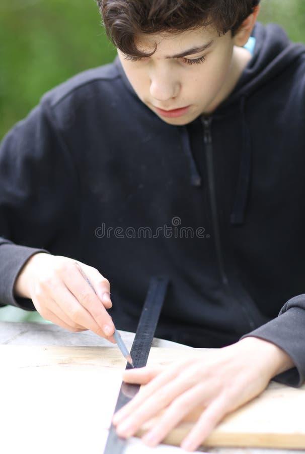 """Έφηβος ξυλουργός μετρά ξύλινα σανίδια για να κάνει δουλειές Ï""""Î¿Ï… σπιτιο στοκ φωτογραφία με δικαίωμα ελεύθερης χρήσης"""