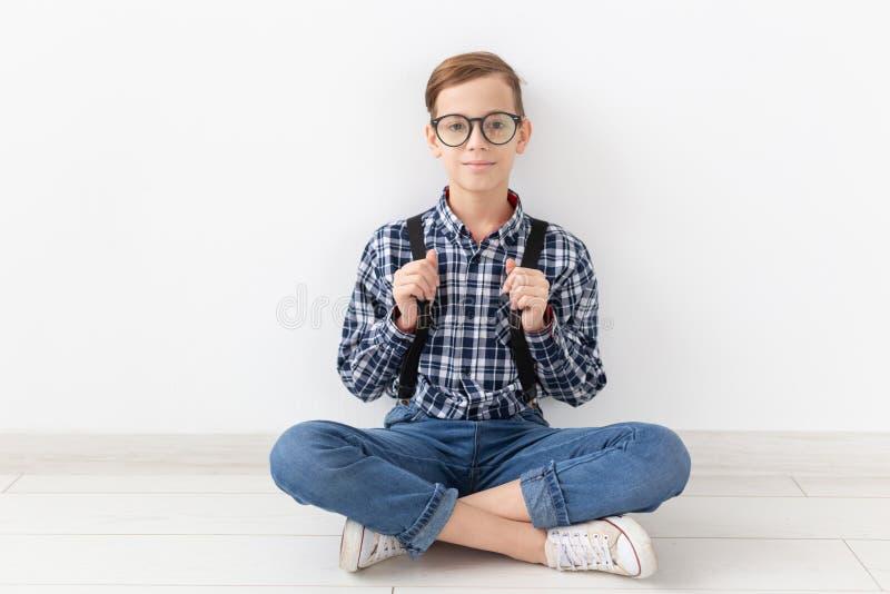 Έφηβος, παιδιά και έννοια μόδας - μοντέρνη συνεδρίαση αγοριών στο πάτωμα πέρα από το άσπρο υπόβαθρο στοκ εικόνες