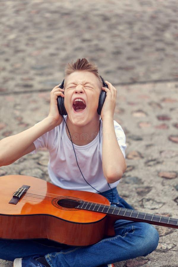 Έφηβος που ακούει τη μουσική στα ακουστικά και το τραγούδι κραυγής Συνεδρίαση νεαρών άνδρων με μια κιθάρα στην οδό στοκ φωτογραφία