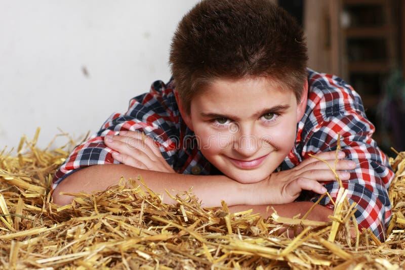 Έφηβος που βρίσκεται σε ένα δέμα αχύρου στοκ φωτογραφία με δικαίωμα ελεύθερης χρήσης