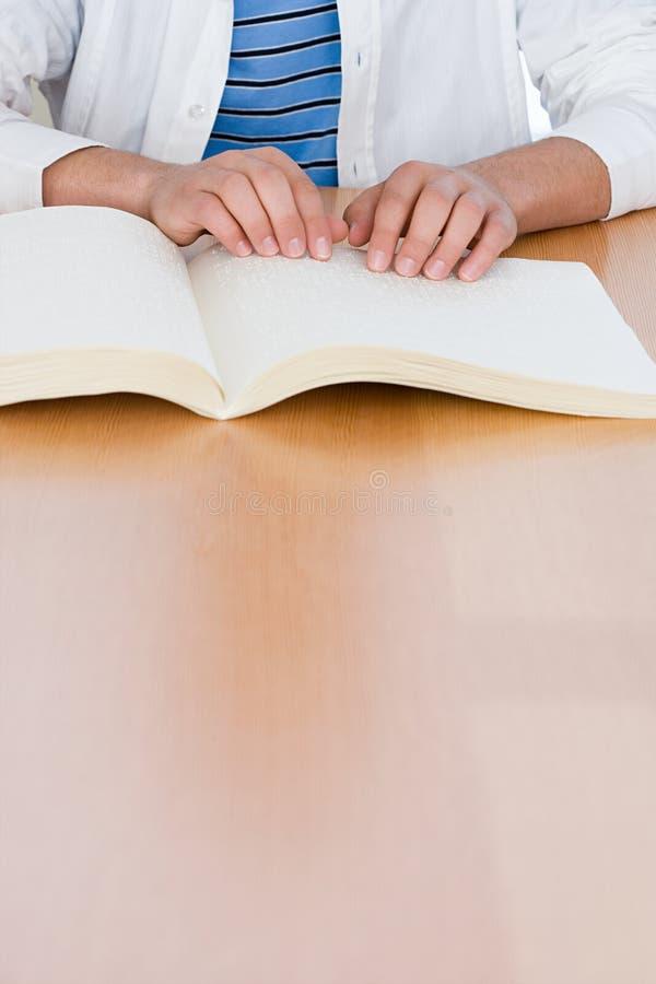 Έφηβος που διαβάζει ένα βιβλίο μπράιγ στοκ φωτογραφίες