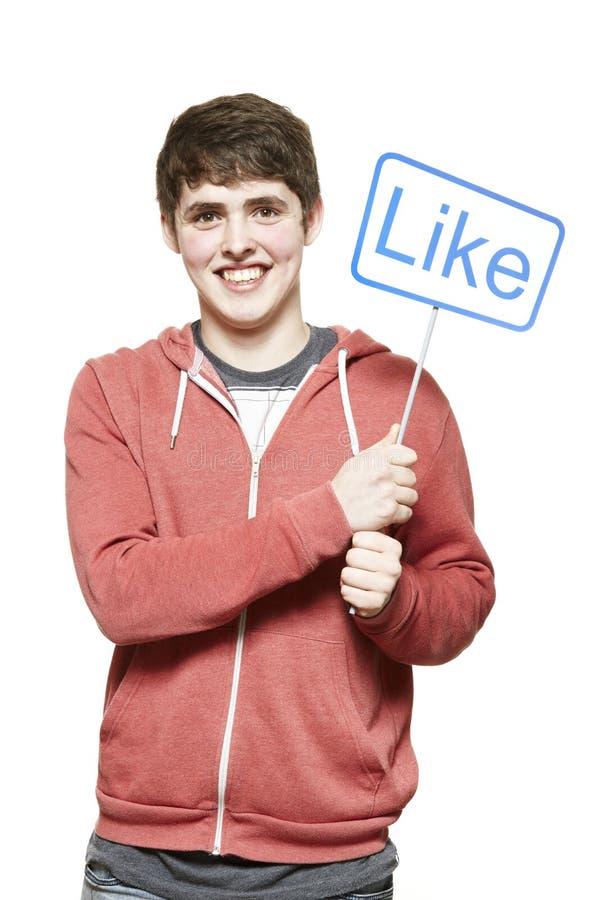 Έφηβος που κρατά ένα κοινωνικό χαμόγελο σημαδιών μέσων στοκ εικόνα με δικαίωμα ελεύθερης χρήσης