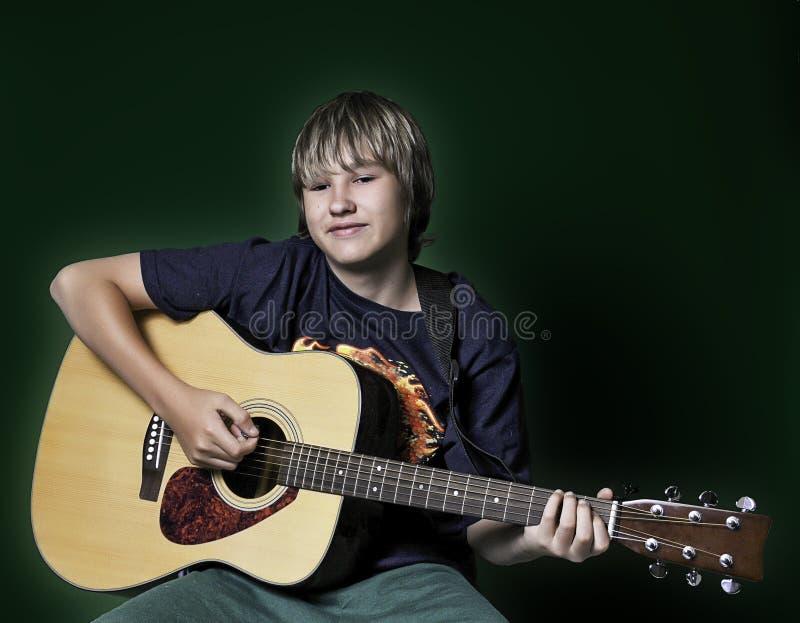 Έφηβος που παίζει μια κιθάρα στοκ φωτογραφίες
