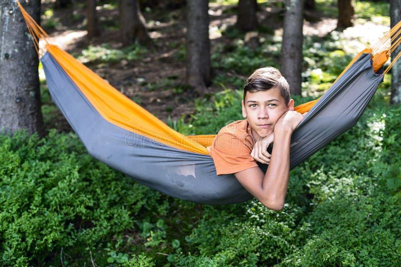 Έφηβος που στηρίζεται σε μια αιώρα Χαλαρώστε κατά τη διάρκεια του ταξιδιού στοκ φωτογραφία με δικαίωμα ελεύθερης χρήσης