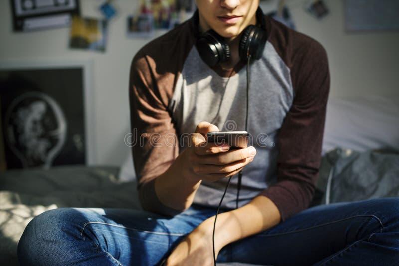 Έφηβος σε μια κρεβατοκάμαρα που ακούει τη μουσική μέσω του smartphone του στοκ φωτογραφίες