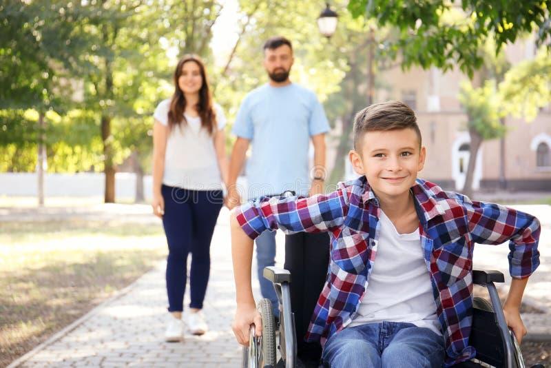 Έφηβος στην αναπηρική καρέκλα με την οικογένειά του που περπατά υπαίθρια στοκ φωτογραφία