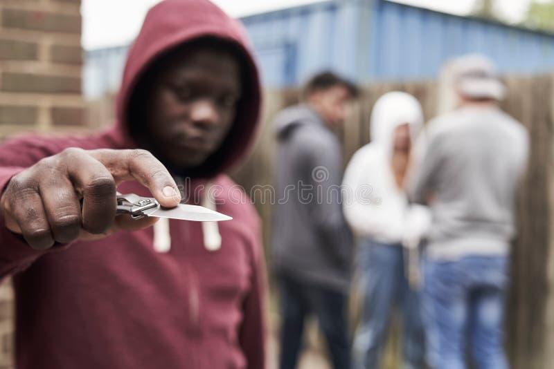 Έφηβος στην αστική συμμορία που δείχνει το μαχαίρι προς τη κάμερα στοκ εικόνες