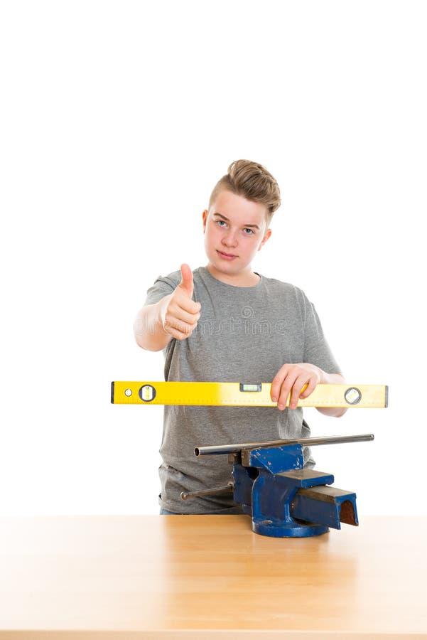 Έφηβος στην επαγγελματική κατάρτιση με το επίπεδο πνευμάτων στοκ φωτογραφία