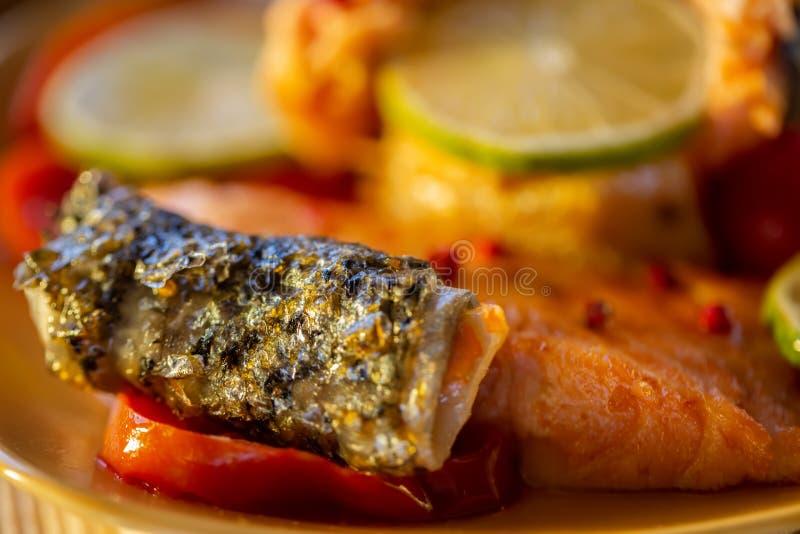 Έψησε έναν σολομό και ένα λεμόνι στη σχάρα Τηγανισμένος χρυσός ένα δέρμα των ψαριών σε μια ντομάτα Μουτζουρωμένο υπόβαθρο στοκ φωτογραφίες με δικαίωμα ελεύθερης χρήσης