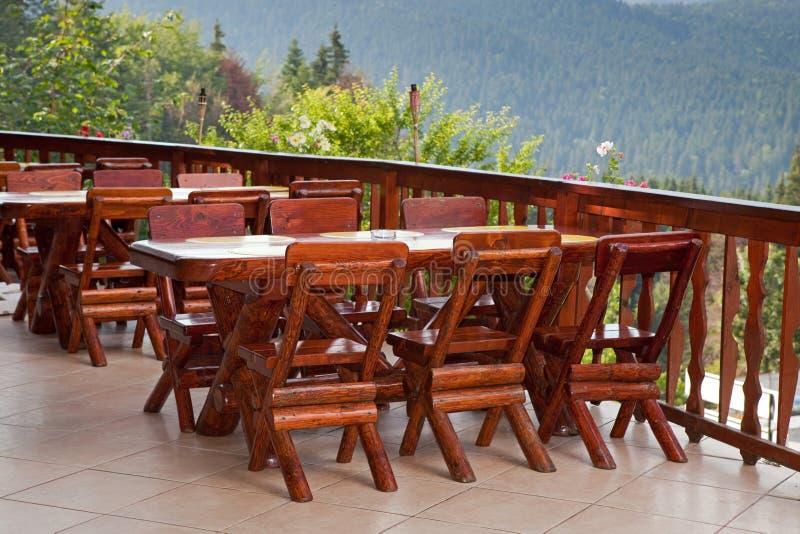 Έδρες και ξύλινος πίνακας σε ένα πεζούλι στοκ εικόνες