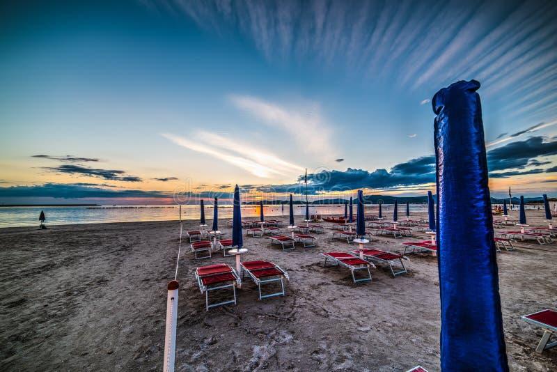 Έδρες και parasol θαλασσίως στο ηλιοβασίλεμα στοκ εικόνα