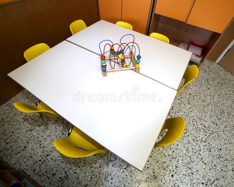 Έδρες με ένα παιχνίδι πέρα από το γραφείο μέσα στον παιδικό σταθμό στοκ φωτογραφίες
