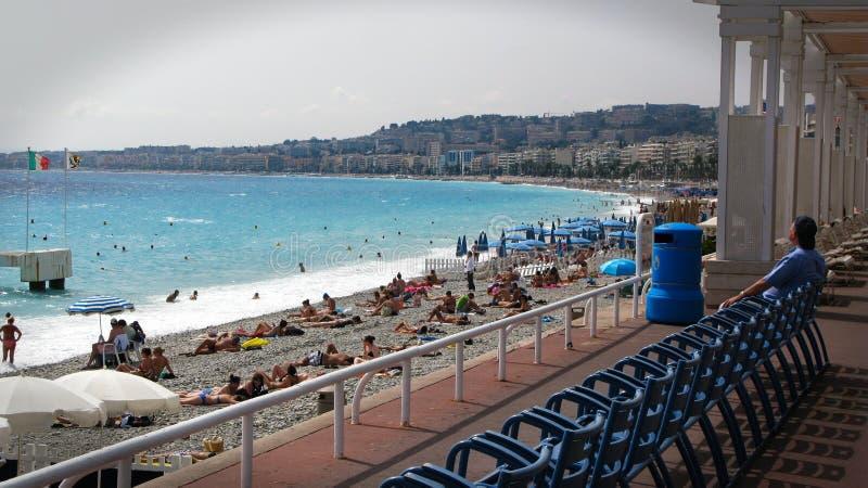 """Ήλιος ανθρώπων που λούζει και που κολυμπά στην παραλία της Νίκαιας στη Γαλλία, το υπόστεγο δ """"Azur και τη Μεσόγειο το καλοκαίρι στοκ φωτογραφίες"""