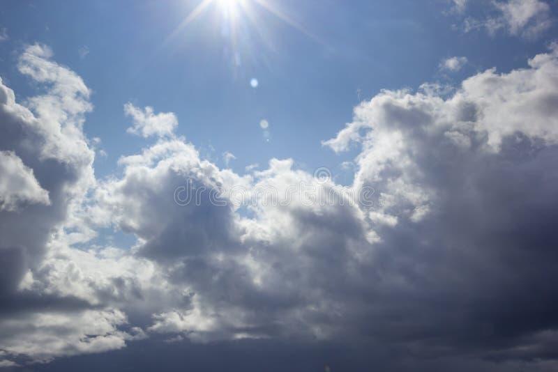 Ήλιος επάνω από το νεφελώδη μπλε ουρανό ημέρας στοκ φωτογραφία