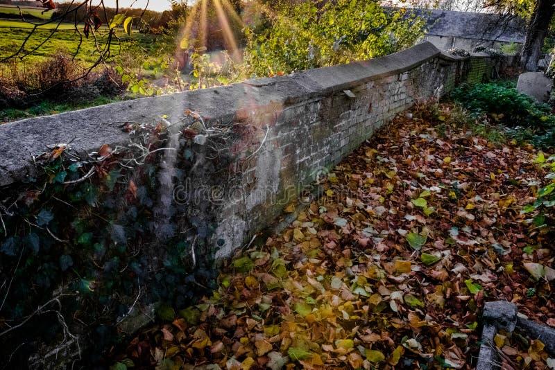 Ήλιος που εκρήγνυται μέσω ενός παλαιού τοίχου πετρών σε ένα αγγλικό νεκροταφείο το χειμώνα στοκ εικόνα