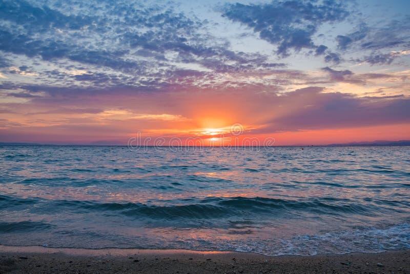 Ήλιος που θέτει πέρα από τον ορίζοντα που απεικονίζει τη θάλασσα με το ζωηρόχρωμο ουρανό ανωτέρω στοκ εικόνες