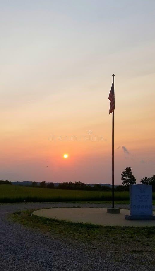 Ήλιος που θέτει στον πόλο σημαιών στοκ εικόνες