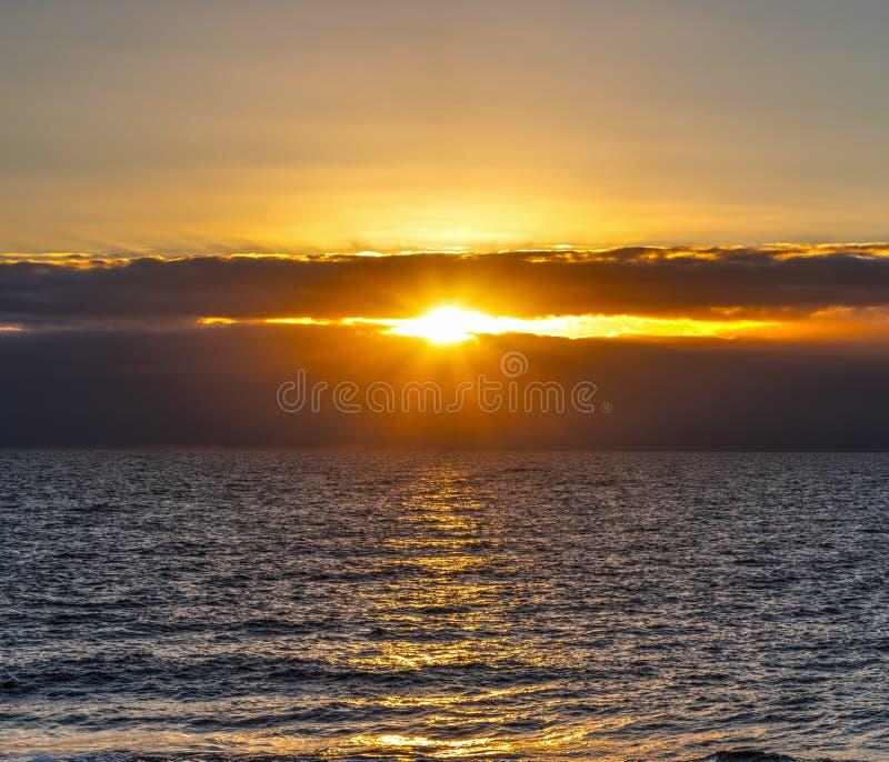 Ήλιος που λάμπει μέσω των σκοτεινών σύννεφων πέρα από τη θάλασσα στο ηλιοβασίλεμα στοκ φωτογραφία με δικαίωμα ελεύθερης χρήσης