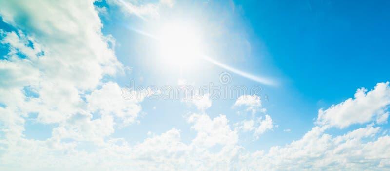 Ήλιος που λάμπει πέρα από έναν μπλε ουρανό με τα άσπρα σύννεφα στοκ φωτογραφίες