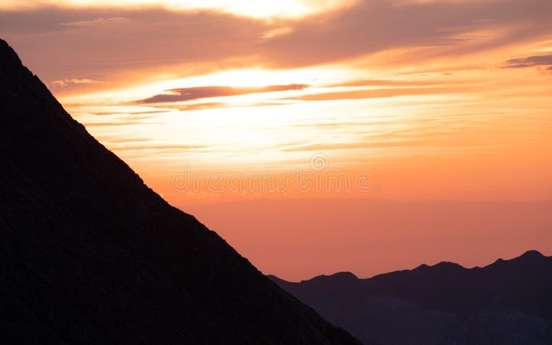 ήλιος που λάμπει πίσω από τη σειρά βουνών, δραματικό ηλιοβασίλεμα στα ελβετικά όρη brienzer rothorn στοκ εικόνα