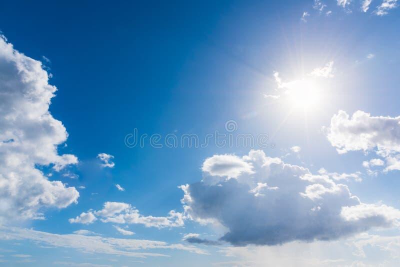 Ήλιος που λάμπει σε έναν μπλε ουρανό με τα άσπρα σύννεφα στοκ εικόνες