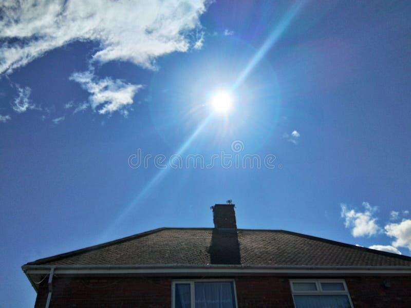 Ήλιος που λάμπει στον ουρανό πέρα από το σπίτι στοκ φωτογραφίες με δικαίωμα ελεύθερης χρήσης