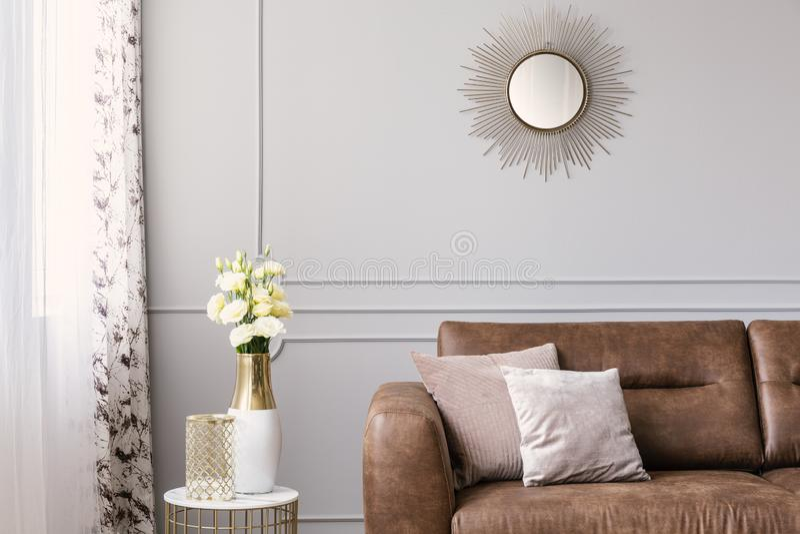 Ήλιος όπως το διαμορφωμένο καθρέφτη επάνω από τον καναπέ δέρματος με τα μαξιλάρια στο γκρίζο κομψό καθιστικό στοκ φωτογραφία με δικαίωμα ελεύθερης χρήσης