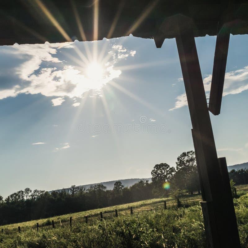 Ήλιος Starburst κάτω από την παραμονή μιας υπαίθριας σιταποθήκης στοκ φωτογραφία