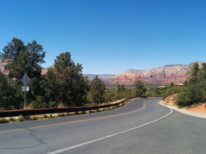 Ήπια δρόμος με πολλ'ες στροφές που οδηγεί στα ζωηρά βουνά στοκ φωτογραφία