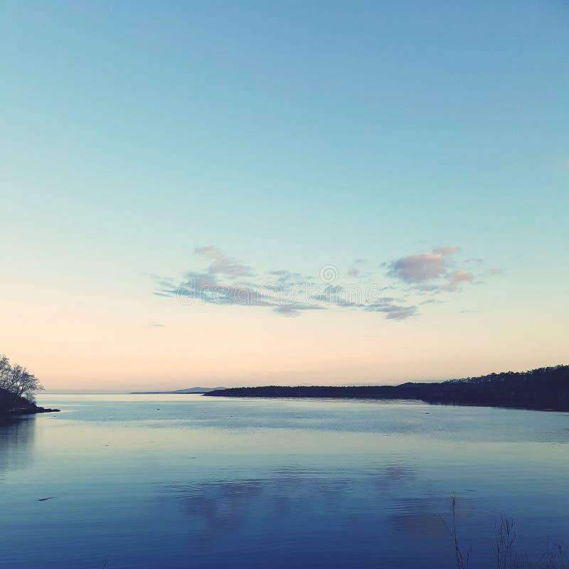 Ήπια το ρόδινο ηλιοβασίλεμα στη θάλασσα wifh φωτίζει τα σύννεφα στοκ εικόνα με δικαίωμα ελεύθερης χρήσης