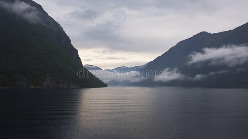 Ήρεμη άποψη από το κρύο, παλιό νερό φιορδ προς τους περιβάλλοντες απότομους βράχους του Geirangerfjord, Νορβηγία στοκ φωτογραφία