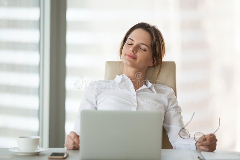 Ήρεμη επιχειρηματίας που κλίνει στην καρέκλα με τις προσοχές ιδιαίτερες στοκ εικόνες