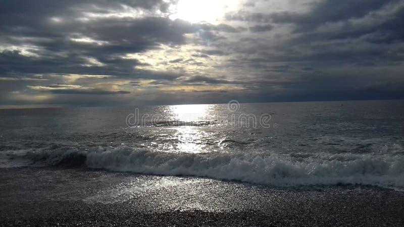Ήρεμη θάλασσα με τα μαλακά κύματα και ήλιος πίσω από τα σύννεφα στοκ εικόνα