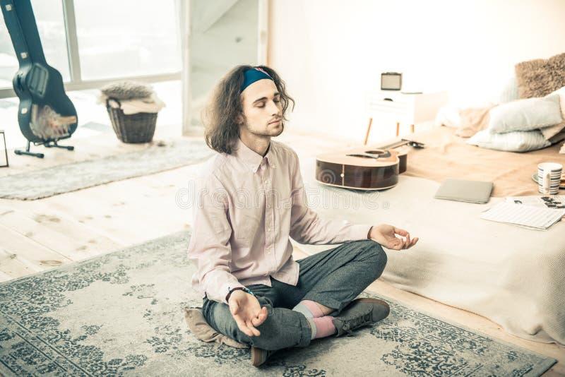 Ήρεμη μοντέρνη συνεδρίαση ατόμων στον τάπητα κοντά στο κρεβάτι του meditating στοκ εικόνες