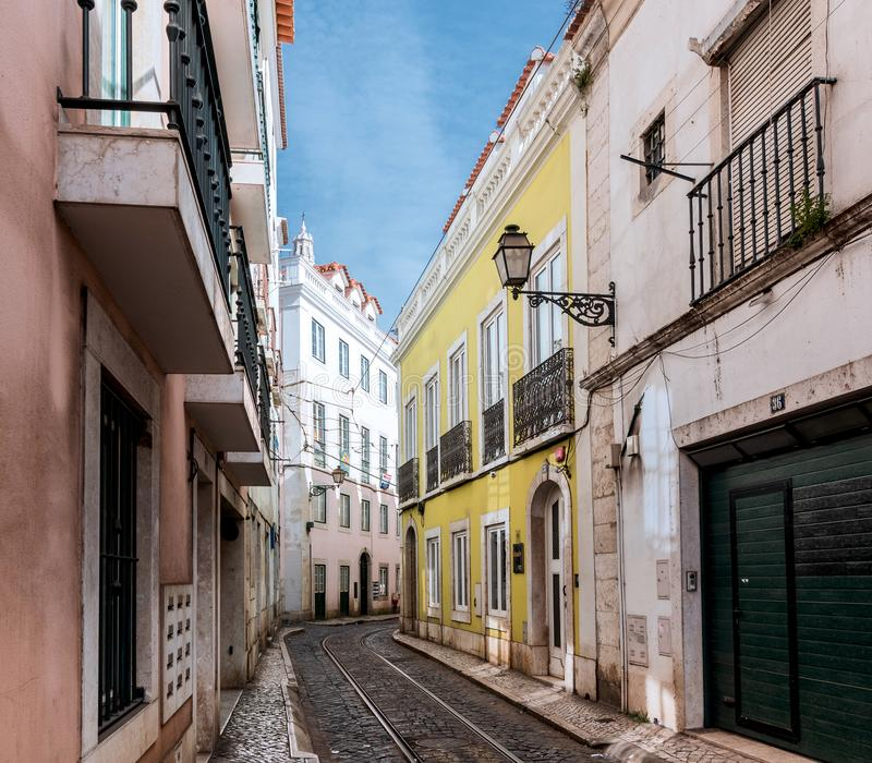 Ήρεμη οδός χωρίς ανθρώπους με τα χρωματισμένα σπίτια, φανάρι, ράγες στη μέση μια ηλιόλουστη ημέρα στοκ εικόνα