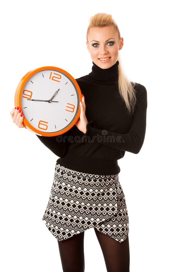 Ήρεμη χαμογελώντας γυναίκα με το μεγάλο πορτοκαλί ρολόι που καμία βιασύνη, enou στοκ φωτογραφία
